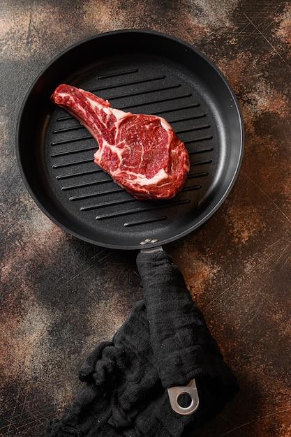 Ковбойский стейк на сковороде для гриля или сырой стейк томагавк, вид сверху Premium Фотографии
