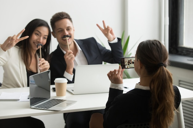 Coworker taking picture on smartphone of colleagues with fake mustache Free Photo