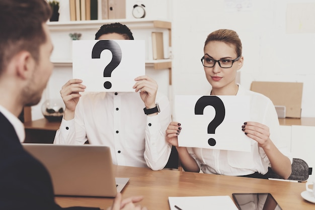 Coworkers are holding question marks at job interview. Premium Photo
