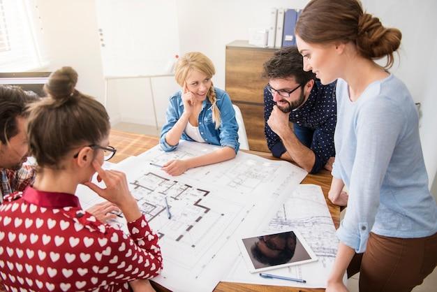 Коллеги в офисе с планами архитектуры и компьютером Бесплатные Фотографии