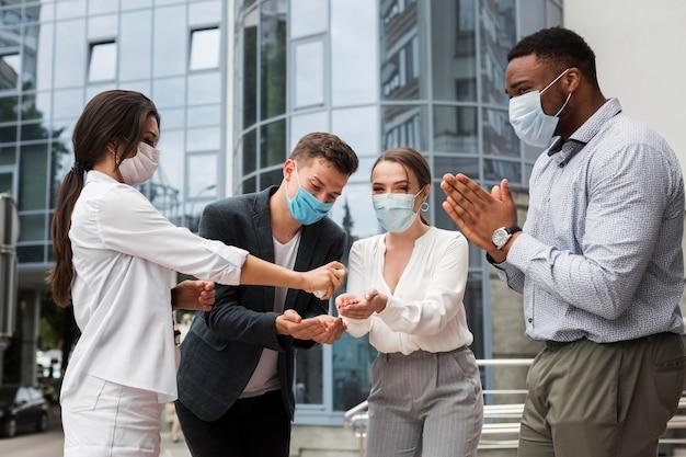 Коллеги дезинфицируют руки на открытом воздухе во время пандемии в масках Бесплатные Фотографии