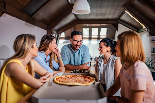 Coworkers eating pizza during work break at modern office. Premium Photo