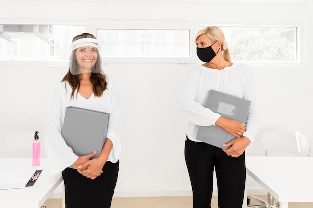 Colleghi che mantengono le distanze sociali e indossano protezioni per il viso Foto Gratuite