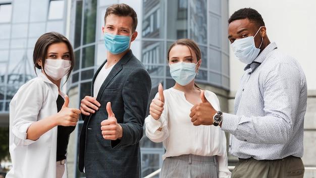 Коллеги на открытом воздухе во время пандемии в масках и поднимают вверх большие пальцы руки Бесплатные Фотографии