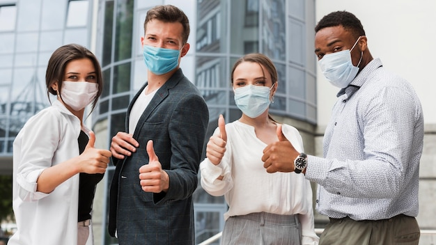 Coworkers outdoors during pandemic wearing masks and giving thumbs up Free Photo