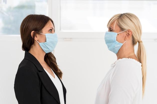 I colleghi che indossano la maschera di protezione al lavoro Foto Gratuite