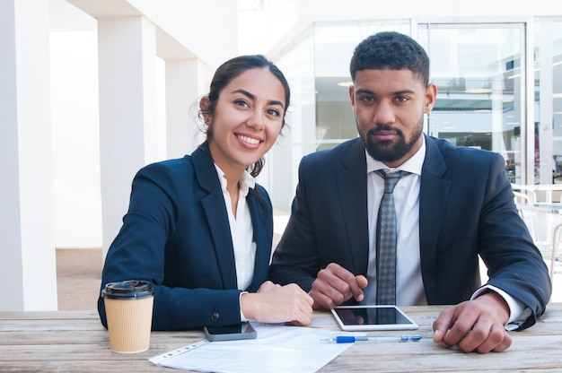 Coworkers working at office desk with tablet, papers and coffee Free Photo