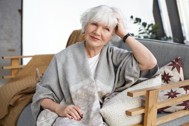 Уют, дизайн интерьера, досуг, образ жизни и концепция пожилых людей. привлекательная элегантная зрелая пенсионерка с морщинами и седыми волосами расслабляется на диване в своем загородном доме, улыбаясь Бесплатные Фотографии