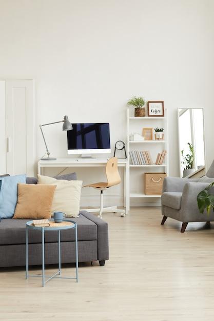 Уютный интерьер квартиры в минималистичном скандинавском дизайне и акцент на серый диван с элементами декора Premium Фотографии