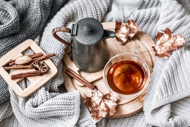 ベッドのある静物シーンで居心地の良い秋の朝の朝食。ホットコーヒーのカップを蒸し、窓の近くに立っているお茶。秋。 Premium写真