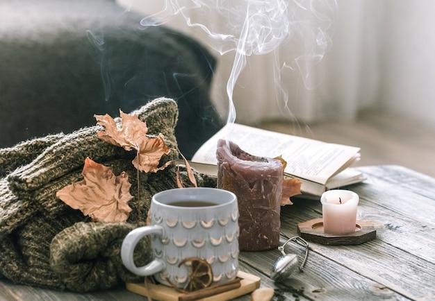 Уютный завтрак утра осени в сцене натюрморта кровати. дымящаяся чашка горячего кофе, чай стоит у окна. Premium Фотографии