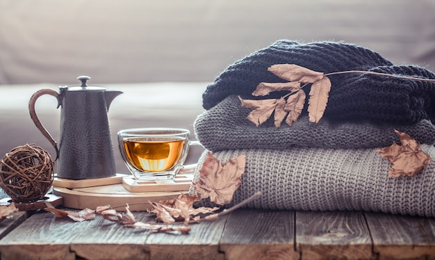 Cozy autumn still life with a cup of tea and decor items in the living room. home comfort concept Free Photo
