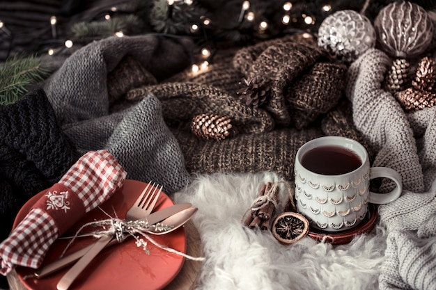 Cozy christmas morning with cup of tea in bed. still life scene with sweaters. steaming cup of hot coffee, tea. christmas concept. Free Photo