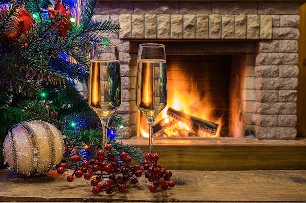 Cozy fireplace. champagne wine before christmas tree decorated ...
