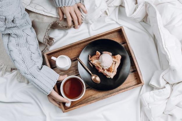 Уютная плоская кровать с деревянным подносом с пирогом, мороженым и черным чаем и женскими руками в сером свитере с чашкой Premium Фотографии