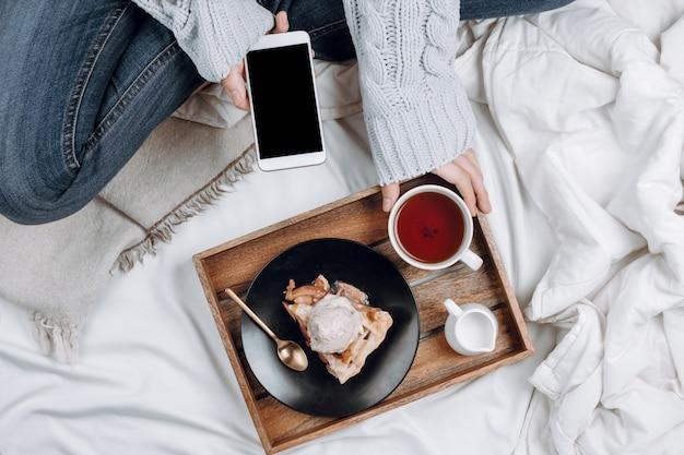 Уютная плоская кровать с деревянным подносом с веганским яблочным пирогом, мороженым и черным чаем, а женщина в джинсах и сером свитере держит смартфон с черным copyspace на белых простынях и одеялах Premium Фотографии