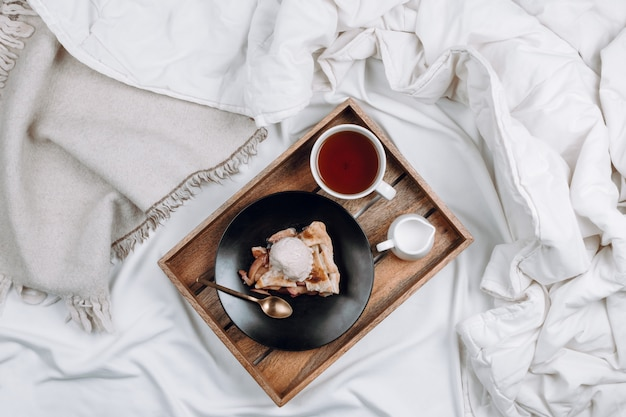 Уютная плоская постель с деревянным подносом с веганским яблочным пирогом, мороженым и черным чаем на белых простынях и одеялах Premium Фотографии