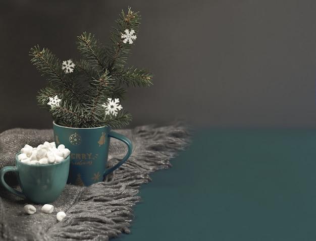 Уютный домашний hugge рождество или новогодний фон с рождественской кружкой с еловыми ветками, снежинками, чашкой кофе или какао с зефиром на сером вязаном пледе на темноте. выборочный фокус. скопируйте пространство. Premium Фотографии