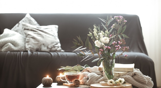Cozy home interior living room with a vase of flowers and candles Free Photo