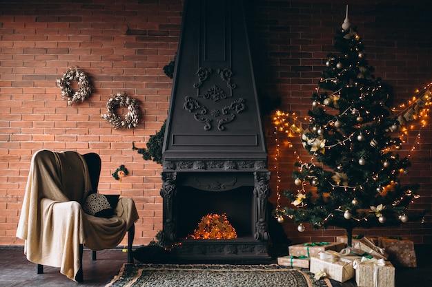 벽난로와 크리스마스 트리가있는 아늑한 거실 무료 사진