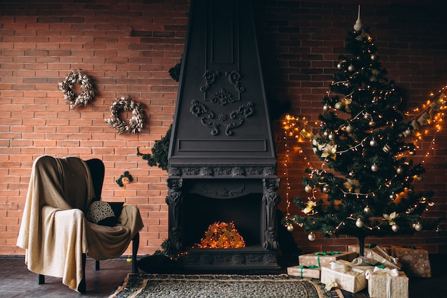 Cozy living room with fireplace and christmas tree Free Photo