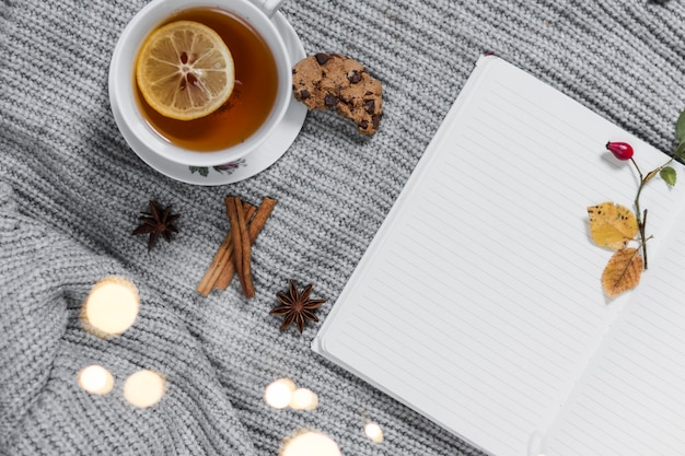 Cozy teatime with notebook on knitted cloth | Free Photo
