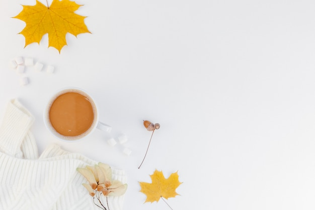 Cozy white warm sweater and coffee cup autumn mood and white background Premium Photo