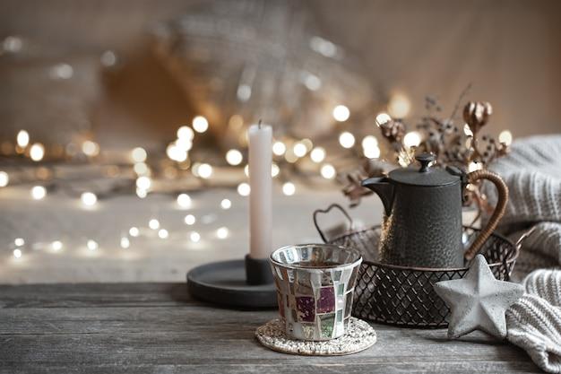Accogliente sfondo invernale con dettagli di decorazioni per la casa su uno sfondo sfocato con luci copia spazio. Foto Gratuite