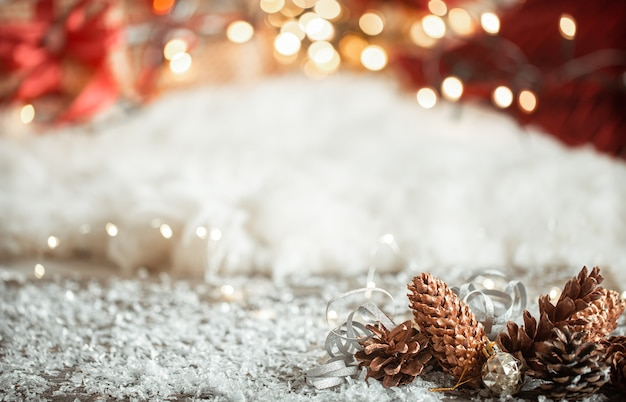 Cozy winter christmas wall with snow and decorative cones copy space. Free Photo