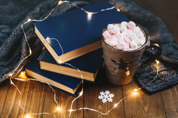 Cozy winter home. big cup of cocoa with marshmallows, warm knitted sweater, books, christmas garland on a wooden table. atmosphere of winter evening. Premium Photo