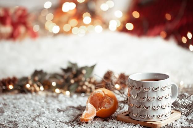 Уютная зимняя стенка с красивой чашкой и мандарином с боке. Бесплатные Фотографии
