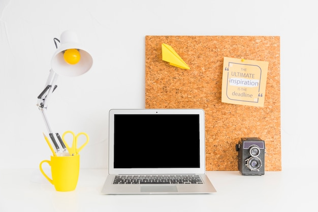 Cozy workplace with cork board and retro camera Free Photo