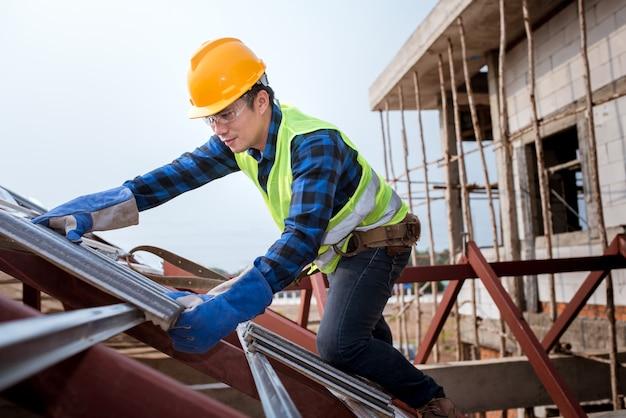 Рабочие, монтирующие крыши в защитной одежде. строительство крыши дома, производство керамической черепицы или черепицы cpac. Premium Фотографии