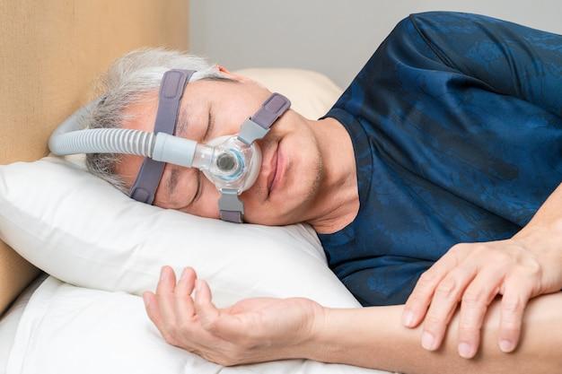 彼の睡眠中にcpapヘッドギアを着ている中年のアジア人 Premium写真