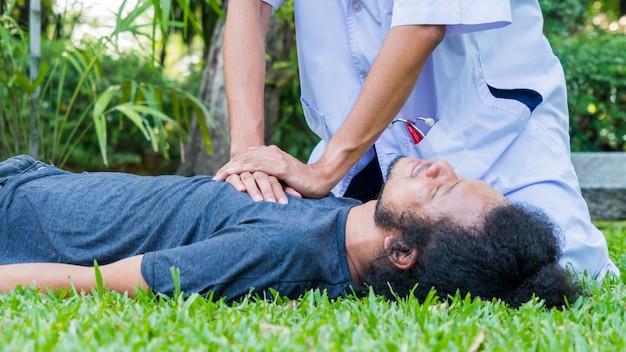 男は草の上に横たわり、医師は白い長袖シャツでcprを助けます Premium写真