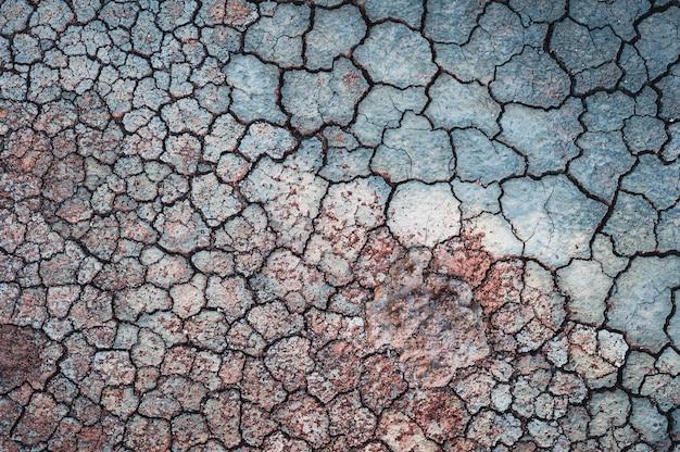 Треснувшая синяя стена с красным песком на ней Бесплатные Фотографии