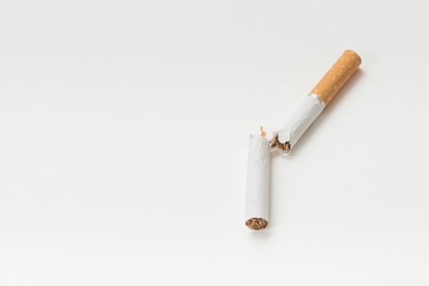 Cracked cigarette above white background Free Photo