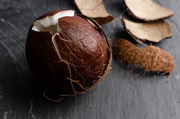 Cracked coconut on dark stone background. Premium Photo