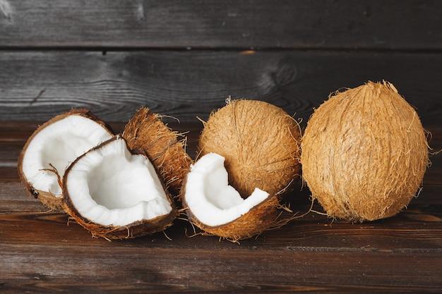 Cracked coconut pieces on dark wooden surface Premium Photo