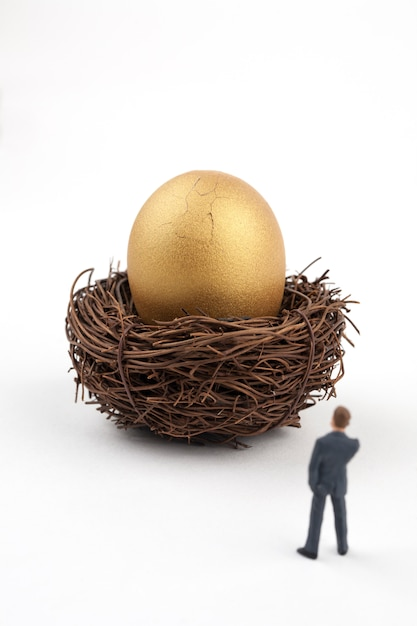 Cracked golden egg and business man Premium Photo