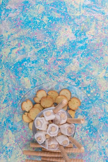 クラッカーとワッフルスティックとロクムのガラス皿 無料写真