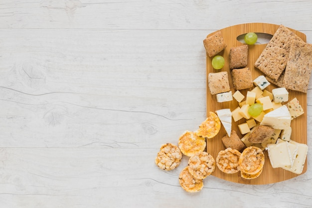 Cracker, cheese blocks, grapes and crisp bread and cookies on chopping board over the desk Free Photo