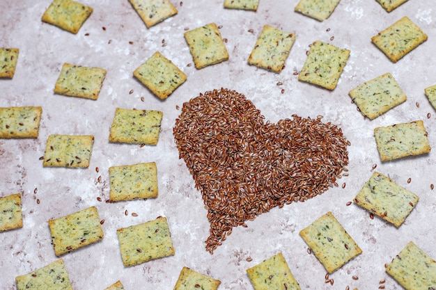 Crackers in shape of heart from linen seeds with olive oil,linen seeds and greens,top view Free Photo