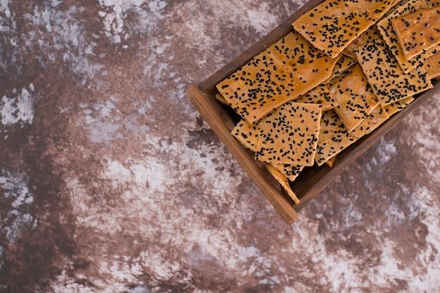 Крекеры с черным тмином на деревянном подносе в верхнем углу Бесплатные Фотографии