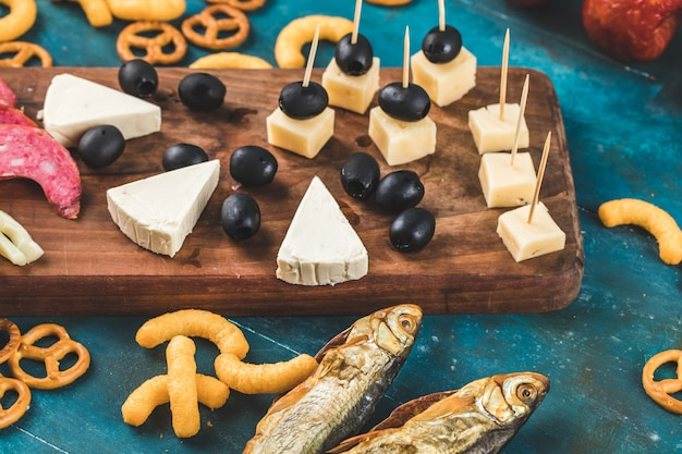 Crackers with smoked fish and cheese on blue background Free Photo