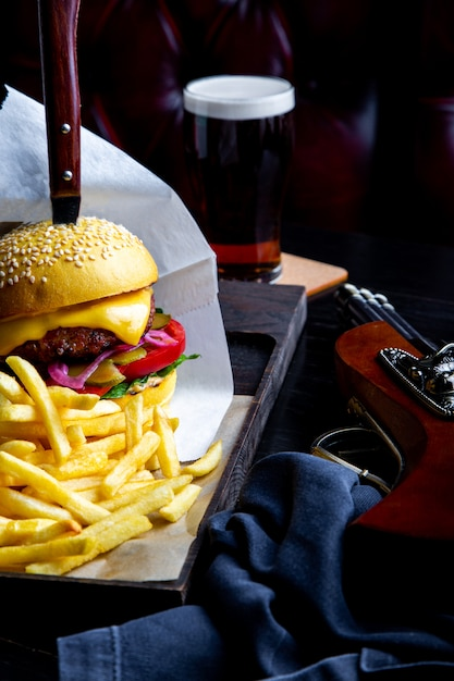 Craft beef burger and french fries on table in restaurant with glass of beer on dark . modern fast food lunch frame Premium Photo