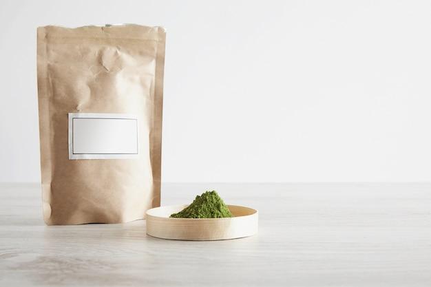 シンプルな背景で隔離の白い木製のテーブルのボックスに茶色の紙袋とプレミアム有機抹茶茶粉を作ります。準備、販売プレゼンテーションの準備ができました。 無料写真
