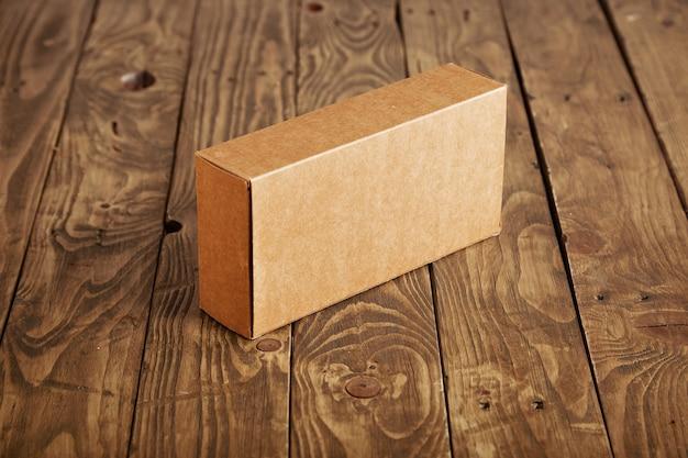 ストレスのかかったブラシをかけられた木製のテーブルに提示されたクラフト段ボールのパッケージボックス 無料写真