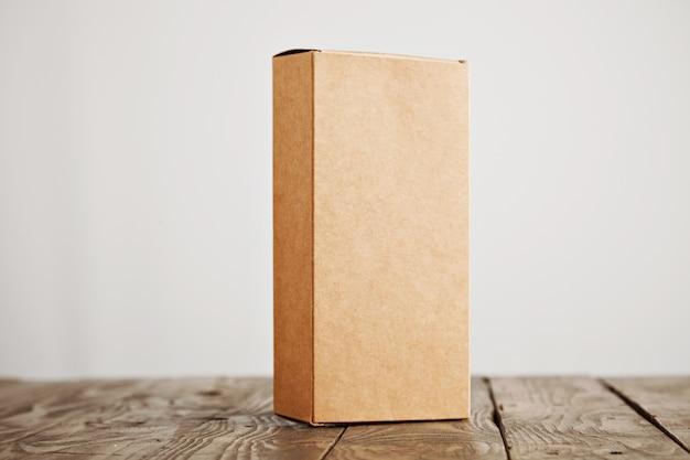 白い背景で隔離のストレスのかかったブラシをかけられた木製のテーブルに垂直に提示されたクラフト段ボールパッケージボックス 無料写真