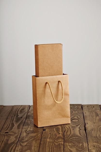 흰색 배경에 고립 된 소박한 나무 테이블에 제시 내부 골 판지 빈 상자와 공예 종이 봉지 무료 사진